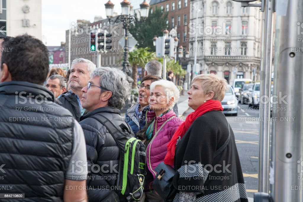 People listening to a tour guide. stock photo