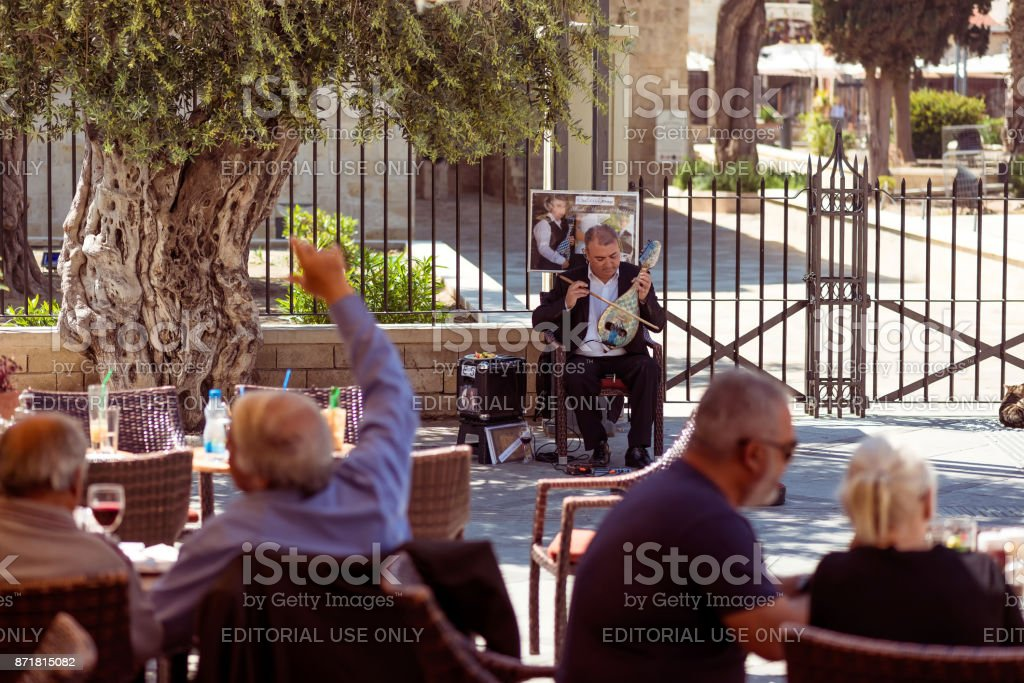 People listening to street musician at Castle Square stock photo