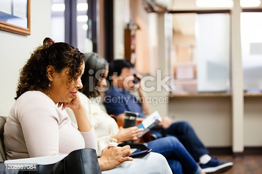 People sit in doctor's waiting room.  One woman looks a medical brochure and a man uses his smart phone to make a call.