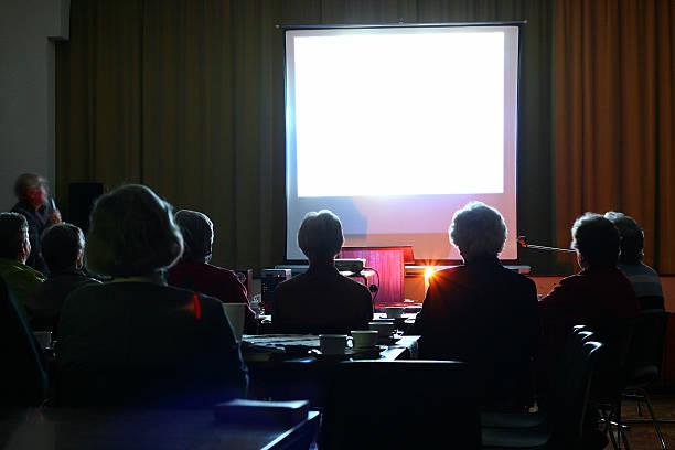 Gens à regarder une présentation en soirée - Photo