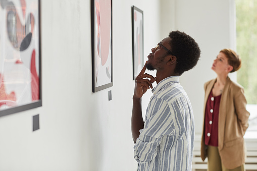 Side view portrait of young African-American man looking at paintings while exploring modern art gallery exhibition, copy space