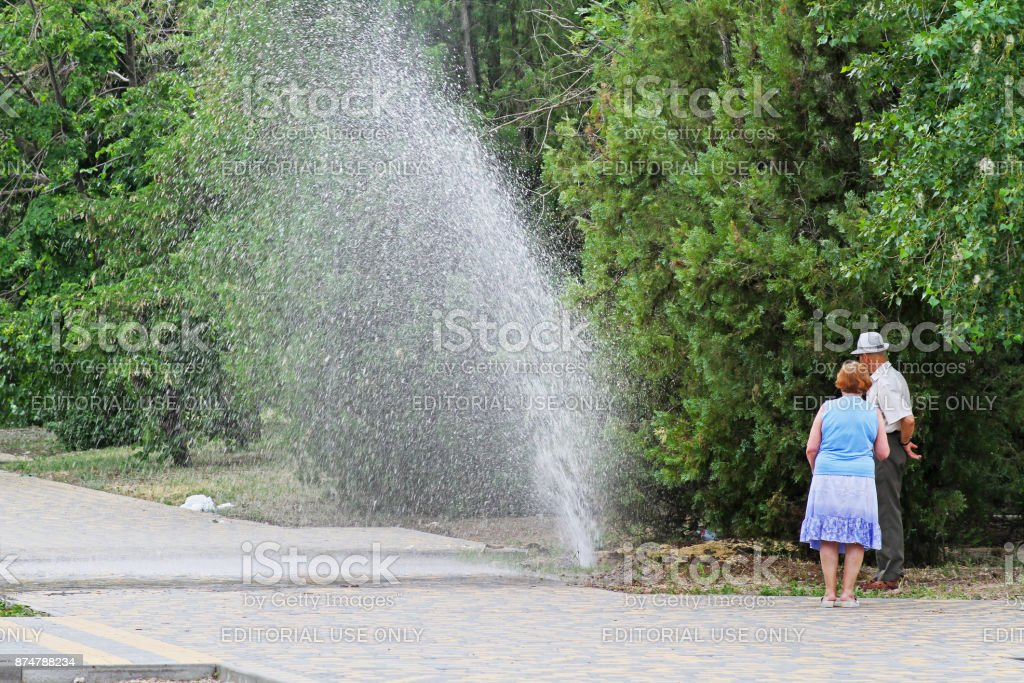 People looking at the broken pipe in the park in Volgograd stock photo