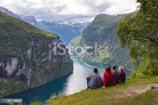 Four people are sitting on the ground and looking at the Geirangerfjord on a cloudy summer day. The rocky mountains are covered with trees.