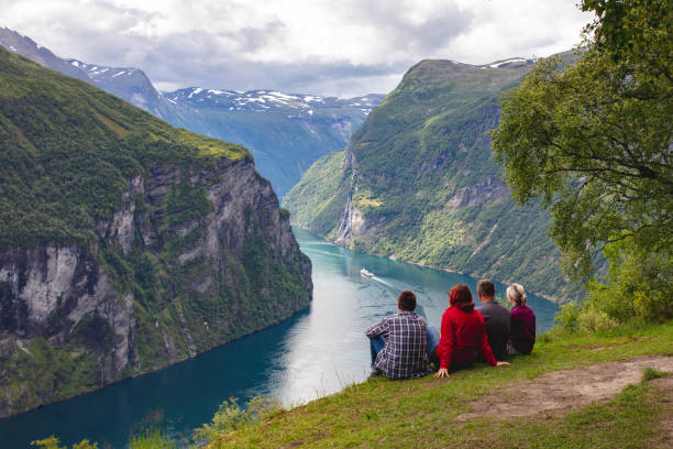 People looking at the Geirangerfjord, Norway Four people are sitting on the ground and looking at the Geirangerfjord on a cloudy summer day. The rocky mountains are covered with trees. norwegian culture stock pictures, royalty-free photos & images