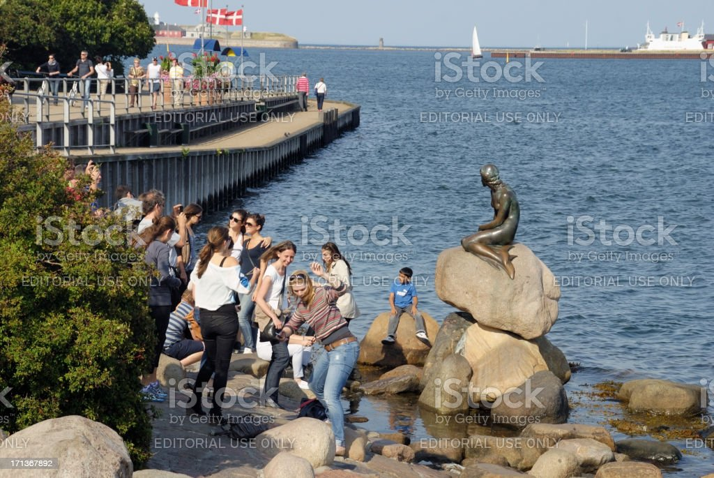 People looking at the Little Mermaid statue in Copenhagen. stock photo