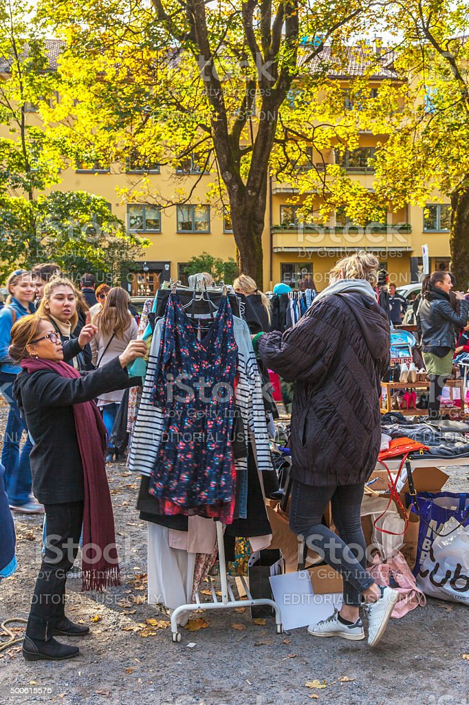 People looking at used clothing and accessories at outdoor market. stock photo