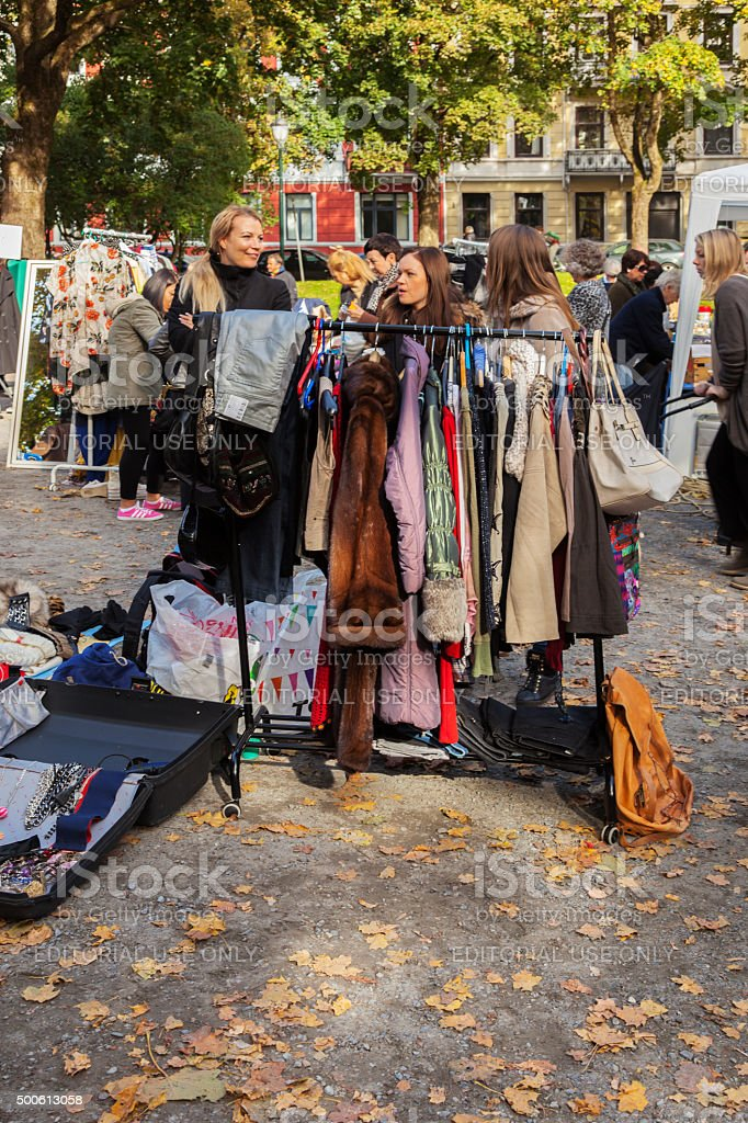 People looking at used clothing and bags at outdoor market. stock photo