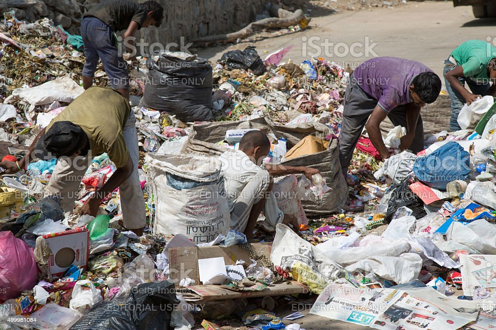 People looking for something in the garbage stock photo