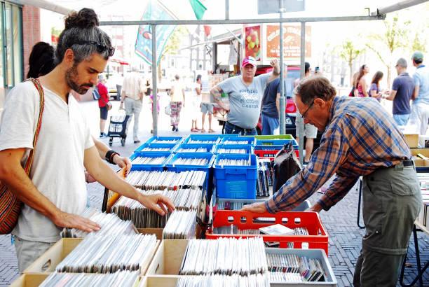 menschen auf der suche nach vintage platten und gebrauchte cds - cd ständer stock-fotos und bilder