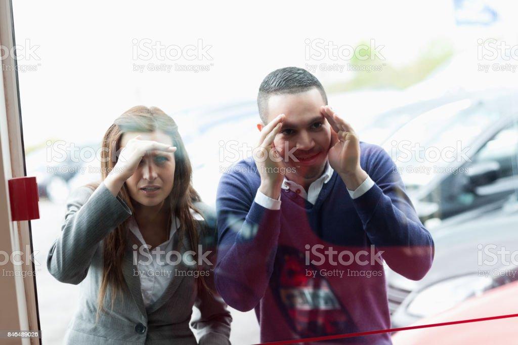 People looking through a shopwindow stock photo