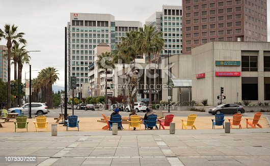 San José, California, USA - May 28, 2018: People lounging in colorful Adirondack chairs at Plaza de Cesar Chavez Park, with a view of Adobe Systems world headquarters, in Downtown San José, Silicon Valley, Northern California.