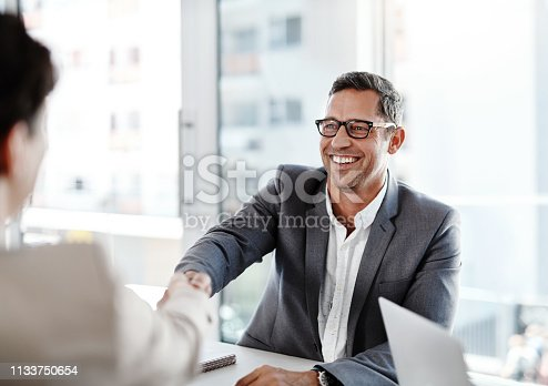Shot of two businesspeople shaking hands in an office
