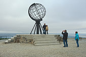 North Cape, Norway - September 05, 2011: Unidentified people make travel photo with symbolic globe at North Cape, Norway. Cliff of North Cape is often referred to as the northernmost point of Europe.