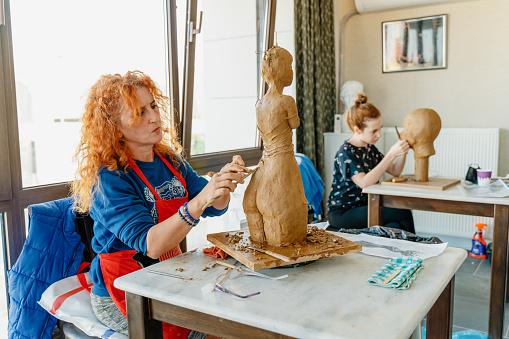 People making sculptures in art studio