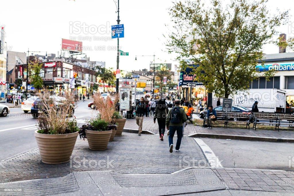 Homem de pessoas andando pela rua de travessia em Fordham Heights centro, cidade de Nova York, Nova York na noite - foto de acervo