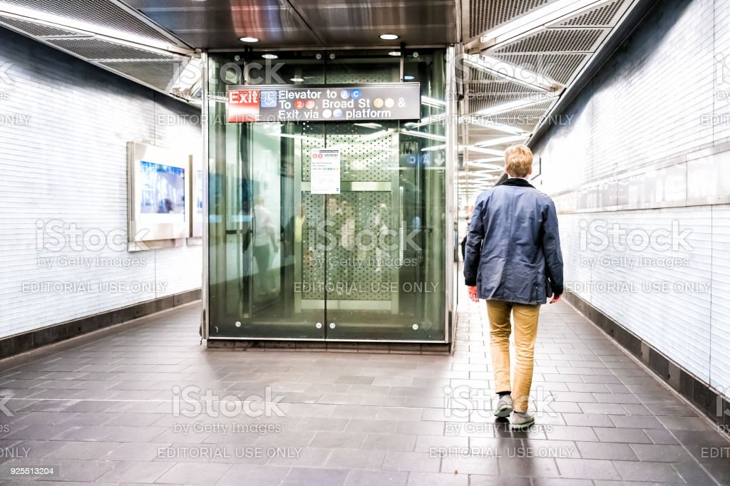 People man walking in underground transit hall corridor transfer to broad street exit, elevator in NYC Subway Station, in downtown stock photo