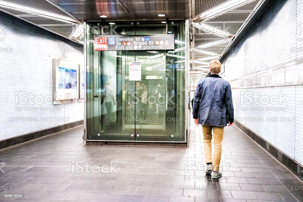Homem de pessoas andando no trânsito subterrâneo corredor corredor transferência para saída rua ampla, elevador na estação de metrô de NYC, no centro da cidade - foto de acervo