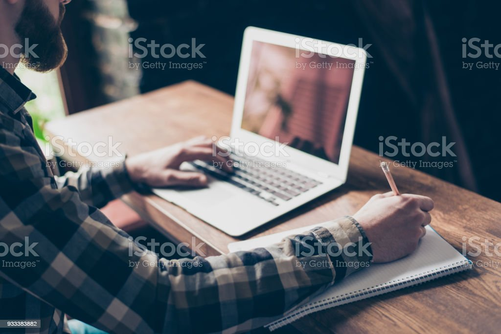People management employment marketing modern technology concept. Cropped close up photo of smart intelligent focused concentrated clever guy doing home task writing information to copybook stock photo