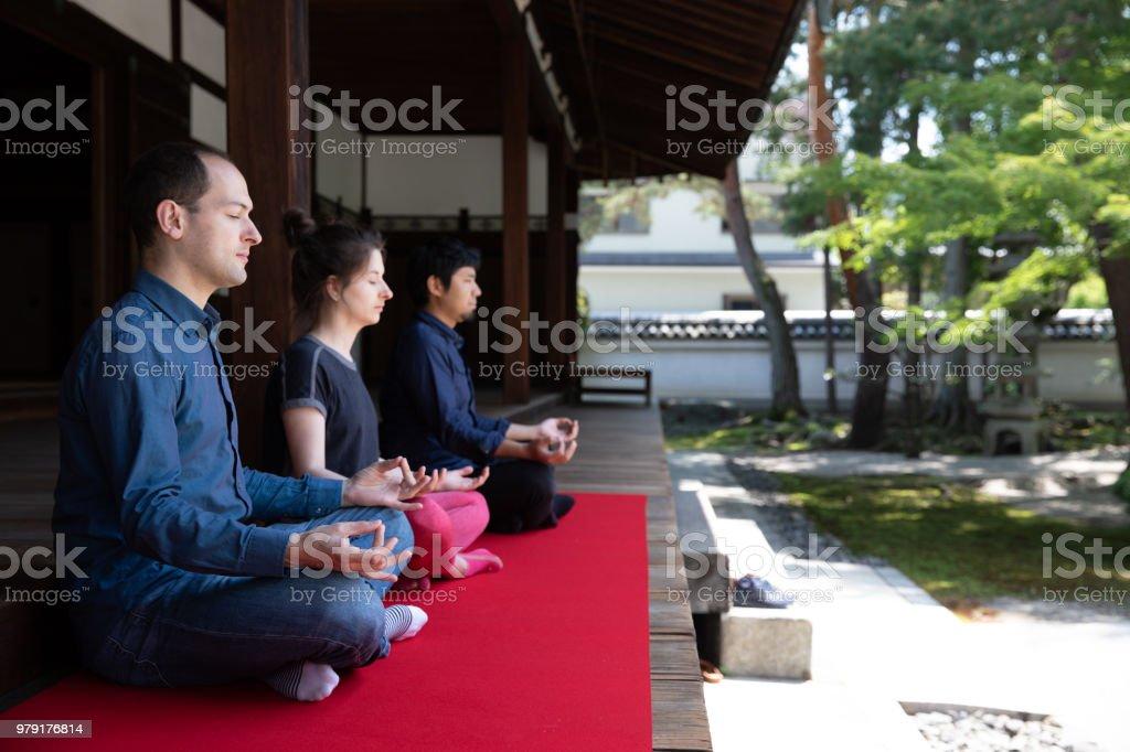 3 people meditating in temple garden stock photo