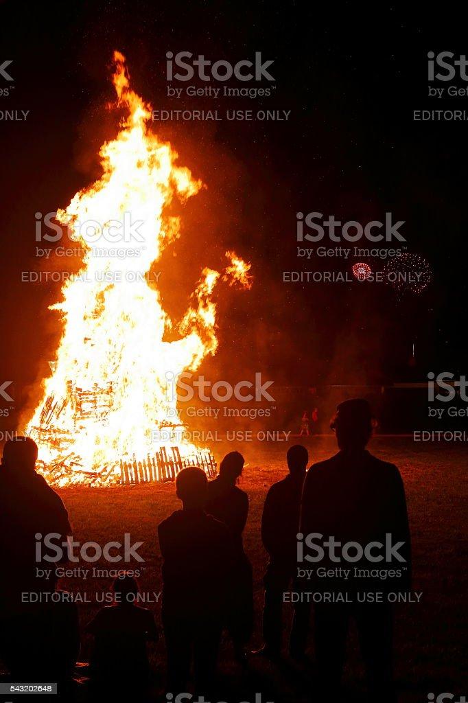 Personnes dans un grand feu de joie avec feux d'artifice en arrière-plan - Photo