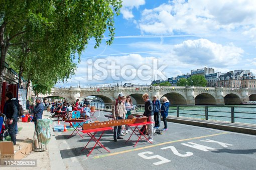 Paris, France - April 25, 2018: People meeting for play games on the quay along the Seine River in Paris