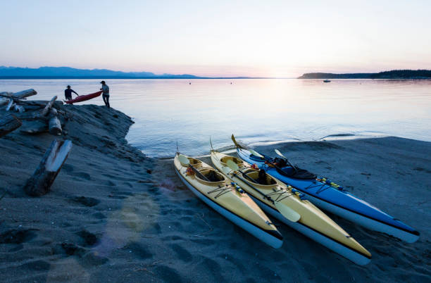 People men friends sea kayaking carrying boats on beach at sunset. Whidbey Island, Washington, United States outdoor adventure water sports travel. People men friends sea kayaking carrying boats on beach at sunset. Whidbey Island, Washington, United States outdoor adventure water sports travel. puget sound stock pictures, royalty-free photos & images