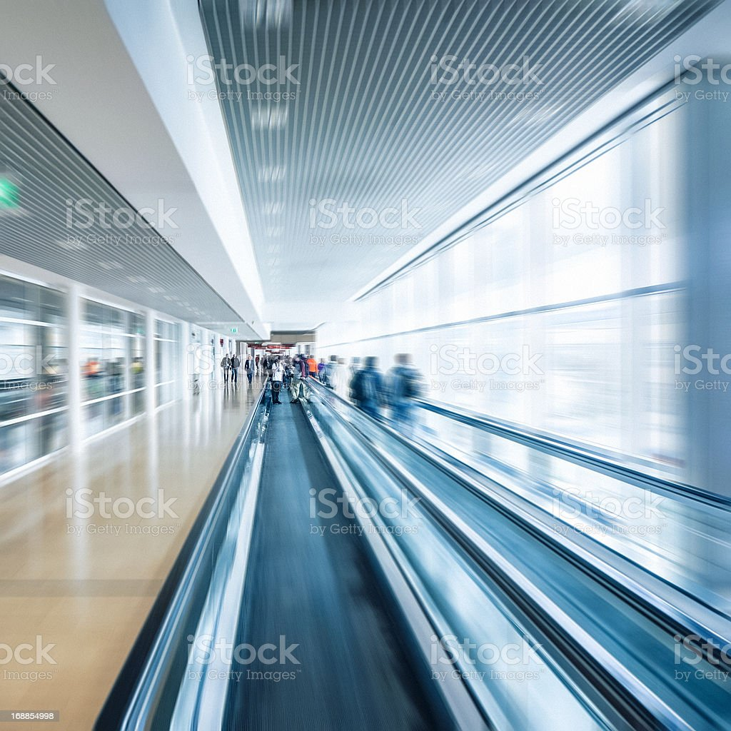 People moving on escalator, walkway in modern office building stock photo