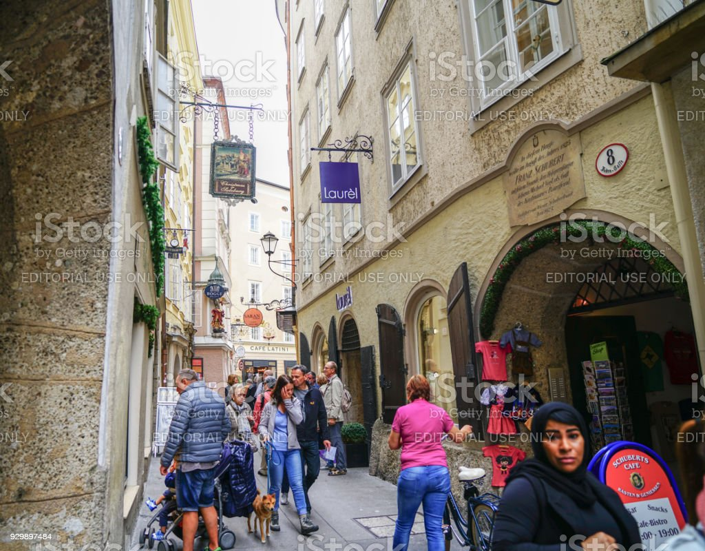 People moving through busy narrow street of historic buildings and modern shops in old city stock photo