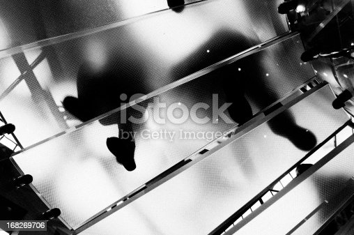 638591126istockphoto People Moving Up Glass Staircase.NYC.Black And White. 168269706