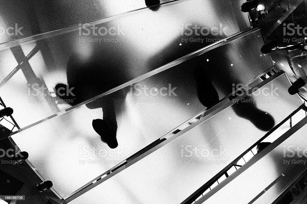 People Moving Up Glass Staircase.NYC.Black And White. stock photo