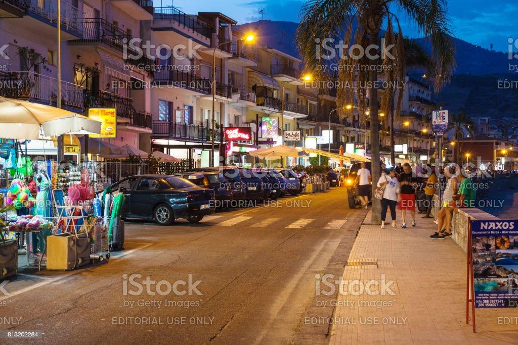 people near gift shops in Giardini Naxos in night stock photo
