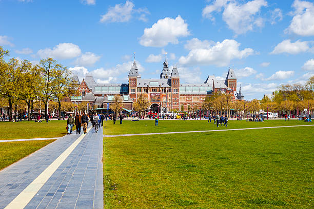 People near Museumplein Amsterdam, Netherlands - May 3, 2016: People, grass field and view of Rijksmuseum, Museumplein museumplein stock pictures, royalty-free photos & images