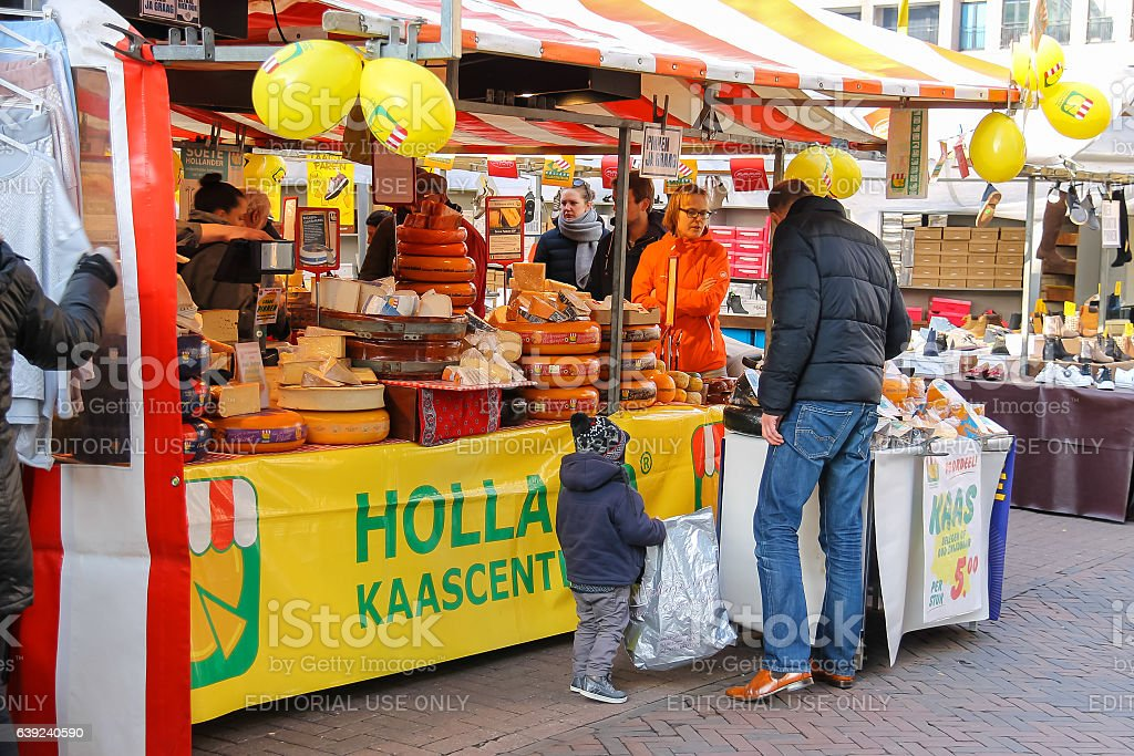 People near shelves with cheese in the street market. Utrecht stock photo