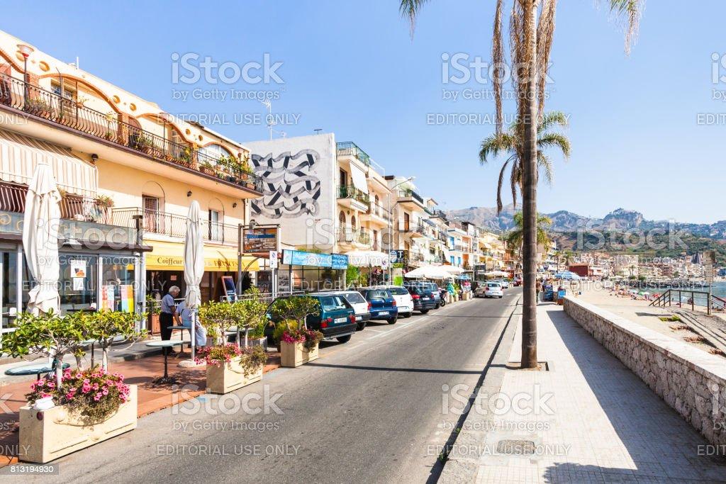 people near shops on waterfront in Giardini Naxos stock photo