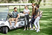 Group of a young friends hanging out together with golf equipment near the golf car on the playing course before the game