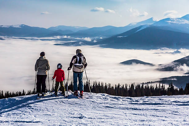 People observing mountain scenery. Family of three people stays in front of scenic landscape. These are skiers, they dressed in winter sport jackets and have skies attached ski holiday stock pictures, royalty-free photos & images