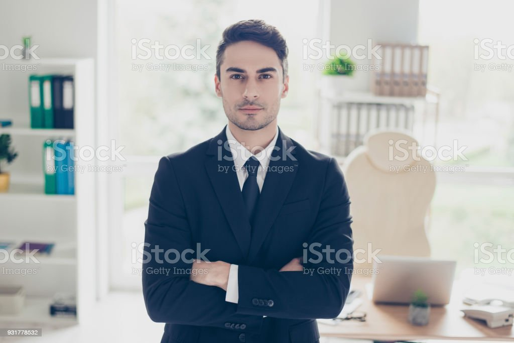 People occupation career profession concept. Portrait of focused concentrated confident experienced qualified clever businessman standing with crossed arms against window in light office stock photo