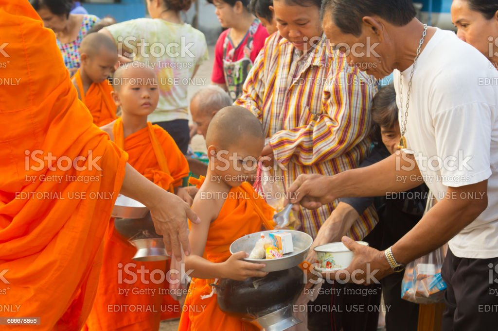 People offer food to the Buddhism novices . stock photo