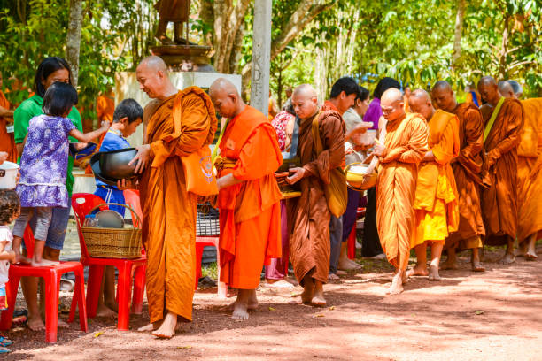 people offering food and things to buddhist monks - religious celebration stock photos and pictures