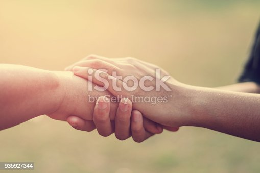 people old and young hand holding with sunset background