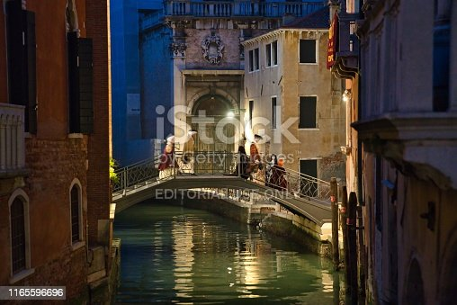 Venice, Italy - March 2, 2019: People with costumes attending the Carnival walking on a lighted bridge in the night, in Venice, Italy.