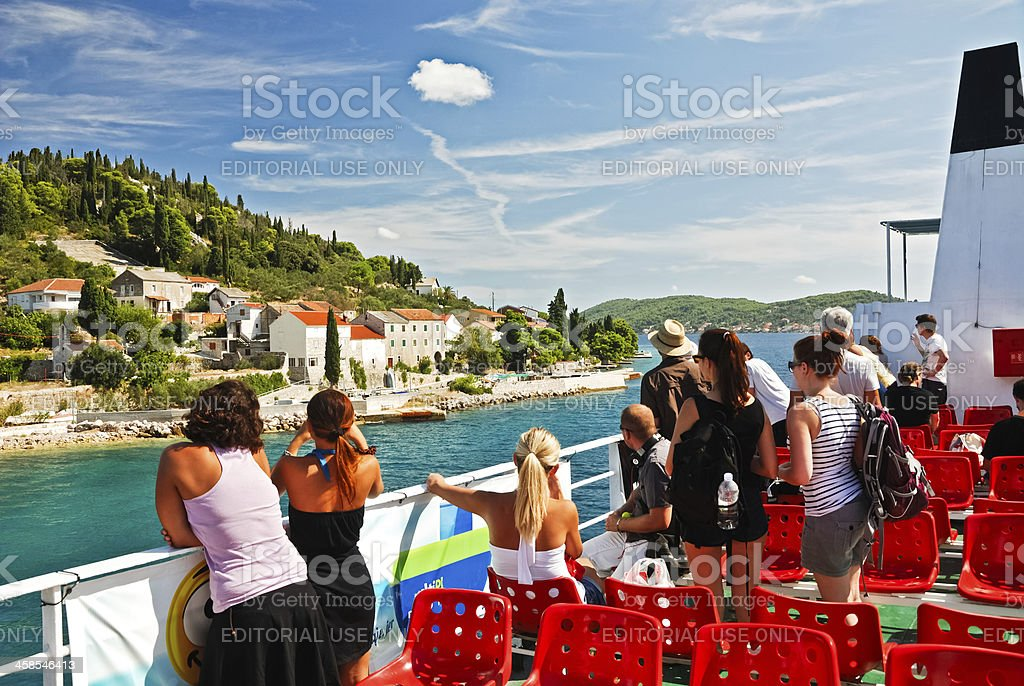 People on a ferry boat watching arrivel to an island stock photo