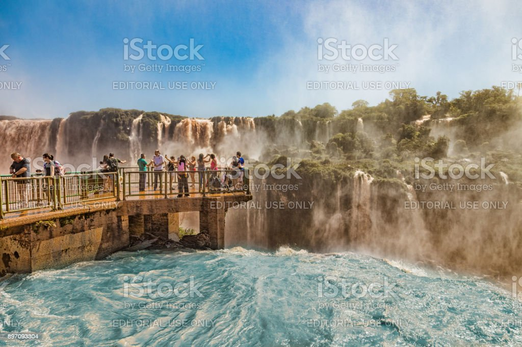 People on a footbridge in the middle of the Iguazu waterfalls on the brazilian side. stock photo