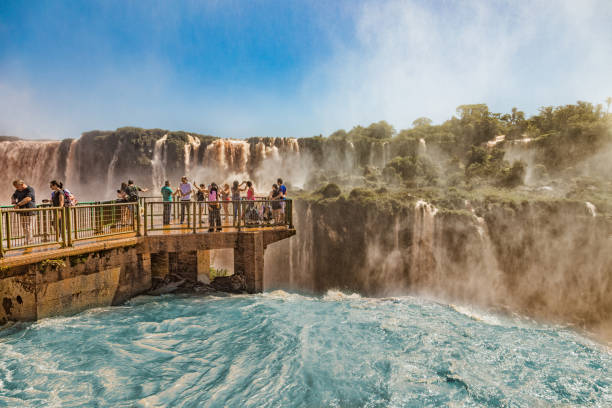 People on a footbridge in the middle of the Iguazu waterfalls on the brazilian side.