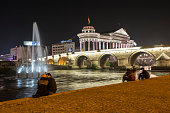 Skopje, Macedonia - August 27, 2013: A man and woman kiss beside the Vardar River, just downstream from the Stone Bridge, in Skopje, Macedonia. The famous bridge connects Macedonia Square to the Old Bazaar.