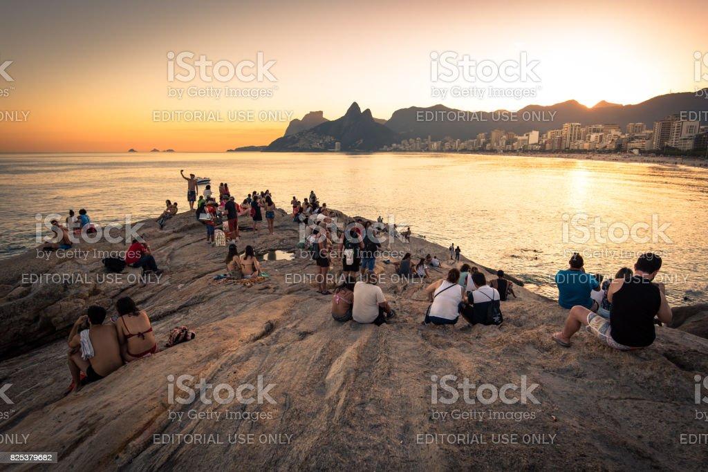 People on Arpoador Rock Enjoying Sunset stock photo