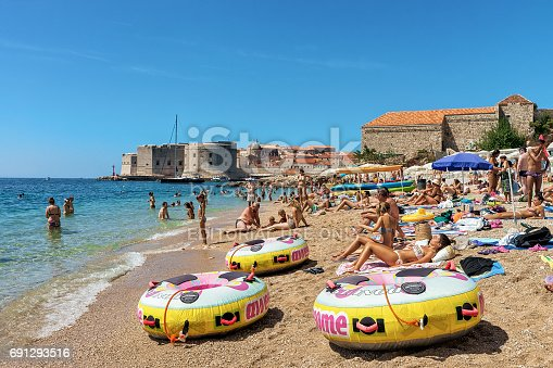 istock People on beach in Adriatic Sea and Dubrovnik fort 691293516
