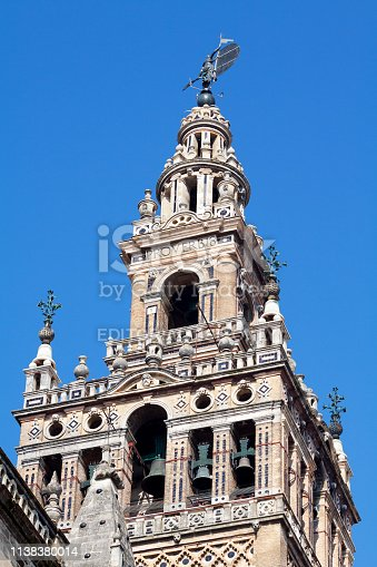 People on bell tower La Giralda in Seville, landmark and lookout of cathedral Maria de le Sede. On top is statue and weather vane in shape of classic roman woman.