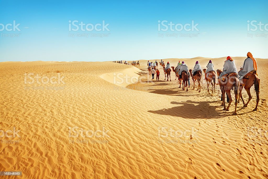 People on camels traveling across the Sahara desert stock photo