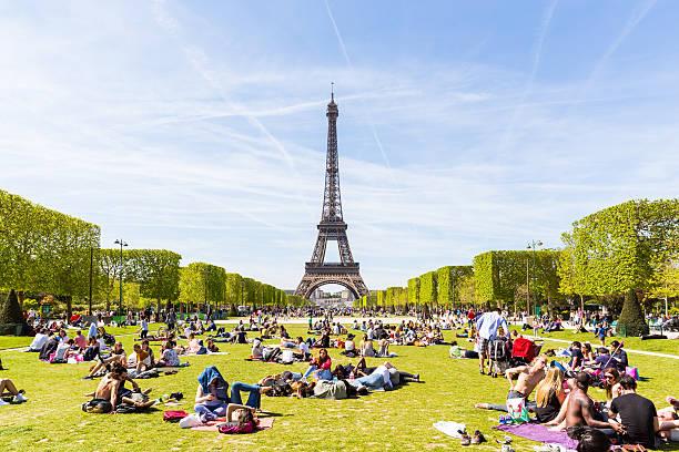 menschen auf dem champ de mars mit eiffelturm im hintergrund - paris sommer stock-fotos und bilder
